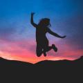 woman jumping at sunset