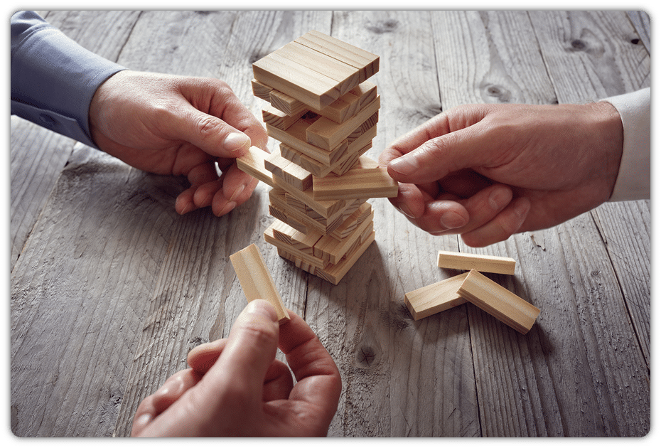 3 hands playing Jenga on wooden table