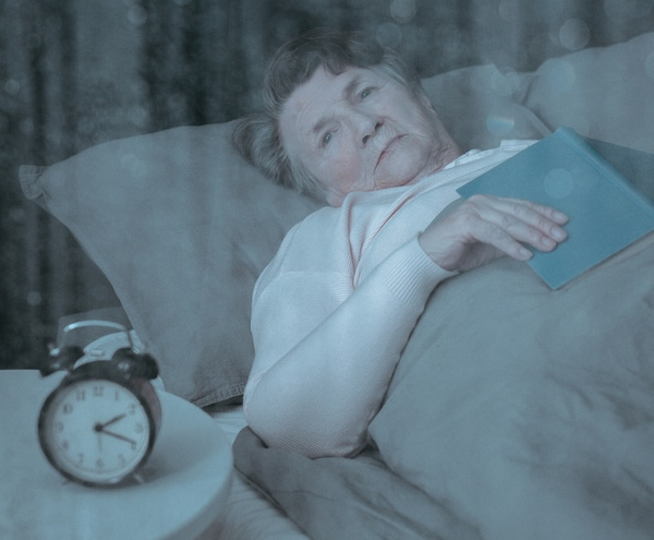 elderly woman lying awake in bed with book attempting to fall asleep