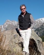Eric Huure standing on top of a mountain summit, leaning on a rock